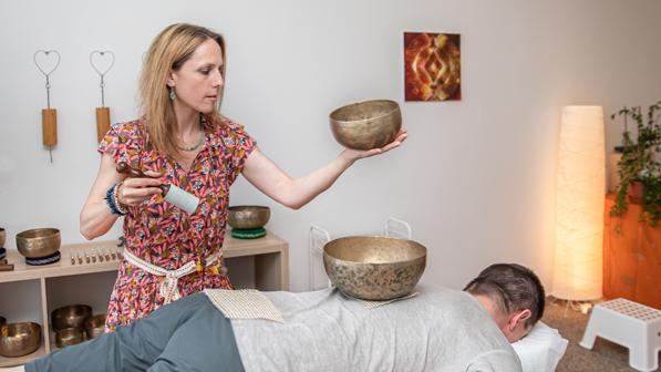 Thérapeute durant un soin de bols chantants pour trouver un équilibre.